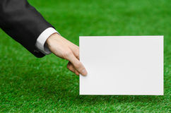 Rabatte und Geschäftsthema: übergeben Sie in einem schwarzen Anzug, der eine weiße leere Karte auf Hintergrund des grünen Grases  Stockfotografie