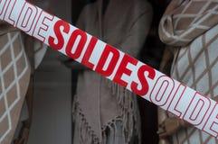 Rabattzeichen 'SOLDES 'auf Französisch auf Fenster im französischen Modespeicherausstellungsraum lizenzfreies stockbild