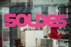 Rabattzeichen 'SOLDES 'auf Französisch, den Traduction von Verkäufen auf Fenster im französischen Modespeicher lizenzfreie stockfotografie