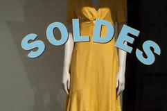 Rabattzeichen auf Fenster im französischen Modespeicherausstellungsraum auf gelbem Sommerkleiderhintergrund stockfotografie