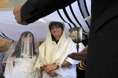 Rabbi belssing Jewish bride and a bridegroom. Under a chupa canopy made out of tallit that represents a Jewish home in a synagog a on their wedding day after stock photos
