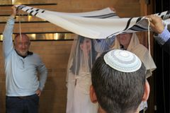 Rabbi belssing Jewish bride and a bridegroom under a chupa. Rear view of a Rabbi belssing Jewish bride and a bridegroom under a chupa canopy made out of tallit royalty free stock photography