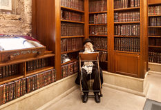 Rabbi and holy books in synagogue. JERUSALEM, ISRAEL - JULY 10, 2014: Old rabbi learns Torah among wooden bookshelves with holy books in Cave Synagogue - old Royalty Free Stock Images