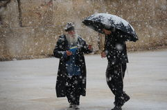 Rabbi teaches under the Jerusalem snow. Picture of rabbi teaching at the Western Wall during snowstorm in Jeri Stock Photo