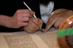 Rabbi writes letter  in the Torah scroll. 