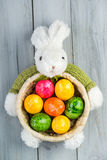 Rabbit basket with colored Easter eggs on wooden background Stock Photo