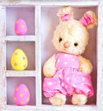 Rabbit bunny toy and easter eggs on the case Stock Photos