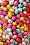 Easter eggs many in a candy glass pot colorful background. A rabbit can lay chocolate eggs. Kids eat chocolate eggs. Easter egg hunt is for families.  At Stock Photos