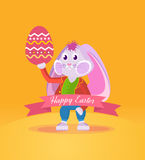 Rabbit in clothes, holding an Easter egg in his hand. Happy easter greeting card. A cute rabbit in beautiful festive clothes, holding an Easter egg in his hand Royalty Free Stock Photos