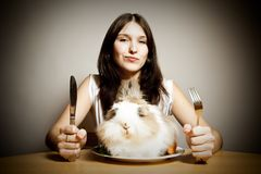 Rabbit For Dinner. A young attractive woman getting ready to enjoy a cute fluffy bunny for dinner. yummy royalty free stock images