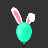 Rabbit ears behind the green baloon Royalty Free Stock Photos