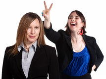 Rabbit Ears Gesture. Professional women holds rabbit ears gesture over a worker Royalty Free Stock Images