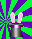 Rabbit ears in magic  hat green and violet sunburst pattern. Rabbit ears appear from the magic cylinder hat  on vibrant colorful green and violet sunburst Stock Photo
