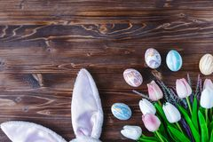 Rabbit ears , tulips and easter eggs on a wooden background royalty free stock images