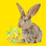 Rabbit with Easter egg. Beautiful little rabbit with multi-colored Easter eggs on an orange background Stock Photo