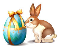A rabbit and an Easter egg with a ribbon. Illustration of a rabbit and an Easter egg with a ribbon on a white background Stock Photography