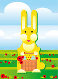 Rabbit with easter eggs. Bunny is carrins easter basket with eggs on a field Stock Photo