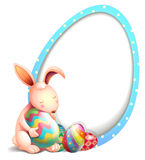 A rabbit with easter eggs beside an egg-shaped signage Royalty Free Stock Photo
