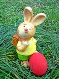 Rabbit finding an egg. Easter rabbit with red egg on grass Royalty Free Stock Photography