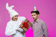 Rabbit giving birthday gift to drunk man over purple background. Royalty Free Stock Image