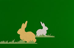 Rabbit and grass on a green background. Colorful rabbits drawn and cut on paper, easter egg on a green background royalty free stock photography
