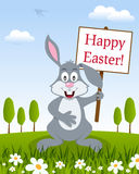 Rabbit with Happy Easter Sign in a Meadow Stock Images