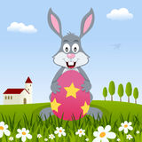 Rabbit Holding a Easter Egg in a Meadow Royalty Free Stock Photography