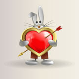 The rabbit is holding a heart with an arrow. Greeting card with a beautiful little Bunny, who is holding a red heart pierced by an arrow as a sign of love and Stock Photography