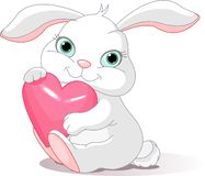Rabbit holds love heart. Small lovely rabbit holds love heart