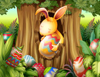 A rabbit inside the hole of a tree surrounded with eggs Royalty Free Stock Photo