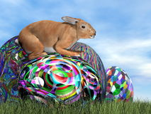 Rabbit on its colorful egg for Easter - 3D render Stock Image