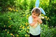 Rabbit kid with bunny ears. Hare toy. Egg hunt on spring holiday. love easter. Family holiday. Little boy child in green. Forest. Happy easter. Childhood royalty free stock photography