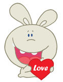 Rabbit laughing and holding a red heart Royalty Free Stock Photography