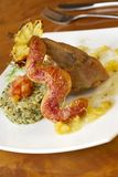 Rabbit leg with green risotto, pineapple sauce and bread sausage Royalty Free Stock Images