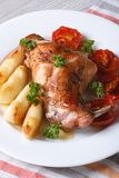 Rabbit leg roasted with apples and tomatoes on a plate closeup. Royalty Free Stock Photography