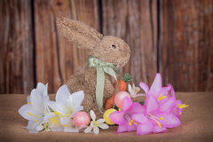 RAbbit with lillies. Easter bunny with lilies and wood background Royalty Free Stock Image