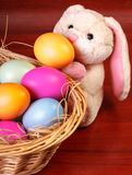 Rabbit near basket with easter eggs Stock Photos