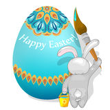 Rabbit paints Easter egg. Royalty Free Stock Photos