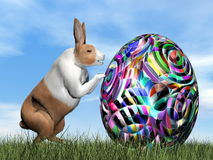 Rabbit pushing one colorful egg for Easter - 3D render Royalty Free Stock Photography