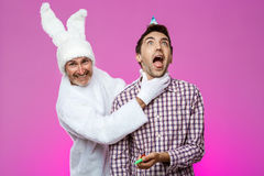 Rabbit smothering drunk man over purple background. Birthday party. Royalty Free Stock Images