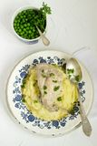 Rabbit in sour cream sauce with tender mashed potatoes and green peas. Rustic style. Royalty Free Stock Photography