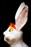 Rabbit statue. Photos statue white rabbit with orange flowers Royalty Free Stock Photos