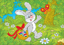 Easter Bunny. Rabbit walking through the forest and carrying his basket with colorful Easter eggs Stock Photography