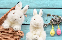 Rabbits in the basket with Easter eggs and pussy willow. On wooden background Stock Images