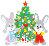 Rabbits and Christmas tree. Little bunnies with a festively decorated green fir Royalty Free Stock Images