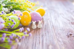 Rabbits with easter eggs on wooden table. Cute Little easter bunny Royalty Free Stock Images