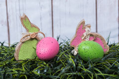 Rabbits and eggs on grass.   Crafted rabbits and decorated eggs Stock Photo