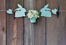 Rabbits, heart, apple flowers on wooden background. Easter. Back Stock Photos