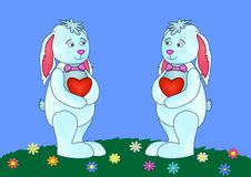 Rabbits with hearts on a meadow Stock Images