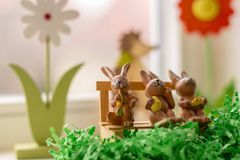 Rabbits sitting on a bench near a window Stock Photo